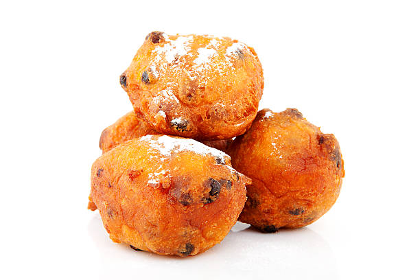 a stack of dutch oliebollen doughnuts on a white background - oliebollen stockfoto's en -beelden