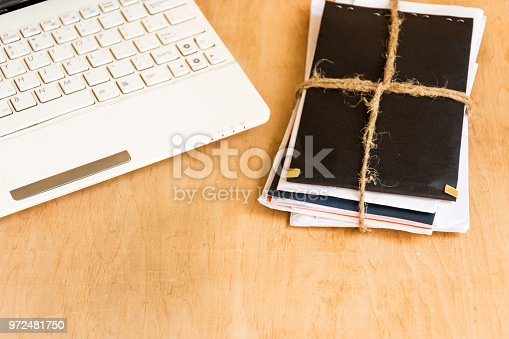 968272356istockphoto Stack of envelopes tied with rope and laptop keyboard on wooden background. 972481750
