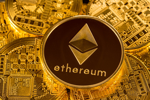 MORGANTOWN, WV - 31 DECEMBER 2017: Ethereum or ether coin lying on top of similar golden coins to illustrate cybercurrencies