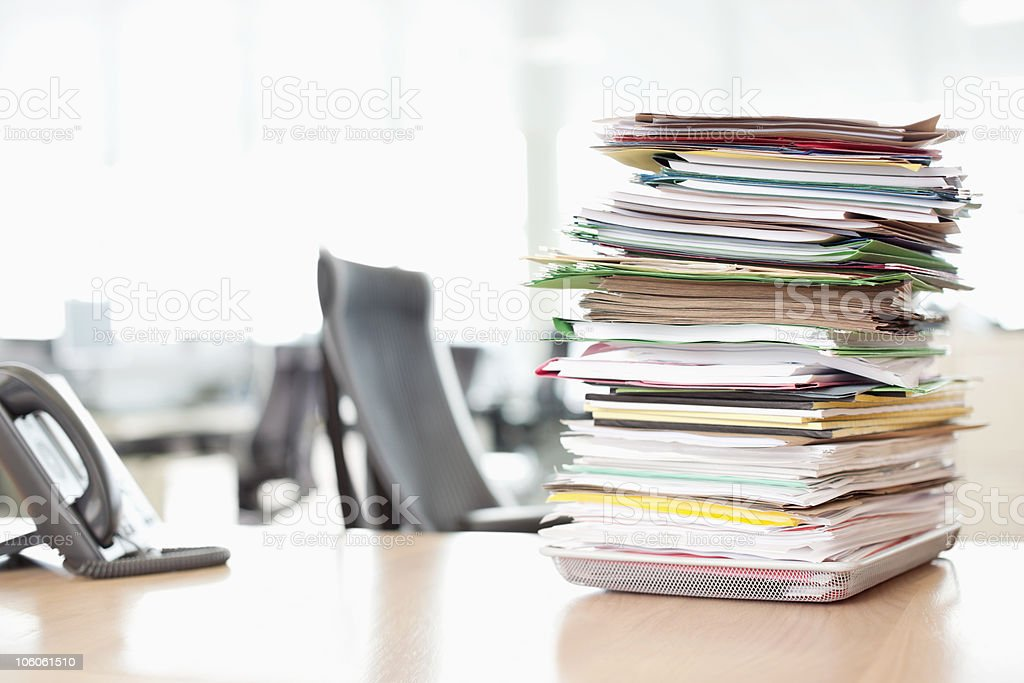 Stack of files on tray next to telephone at office desk royalty-free stock photo