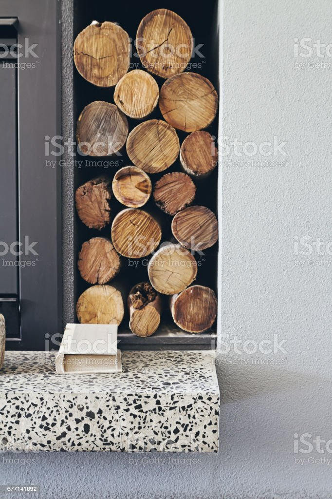 Stack of firewood logs next to fireplace in contemporary home – Foto