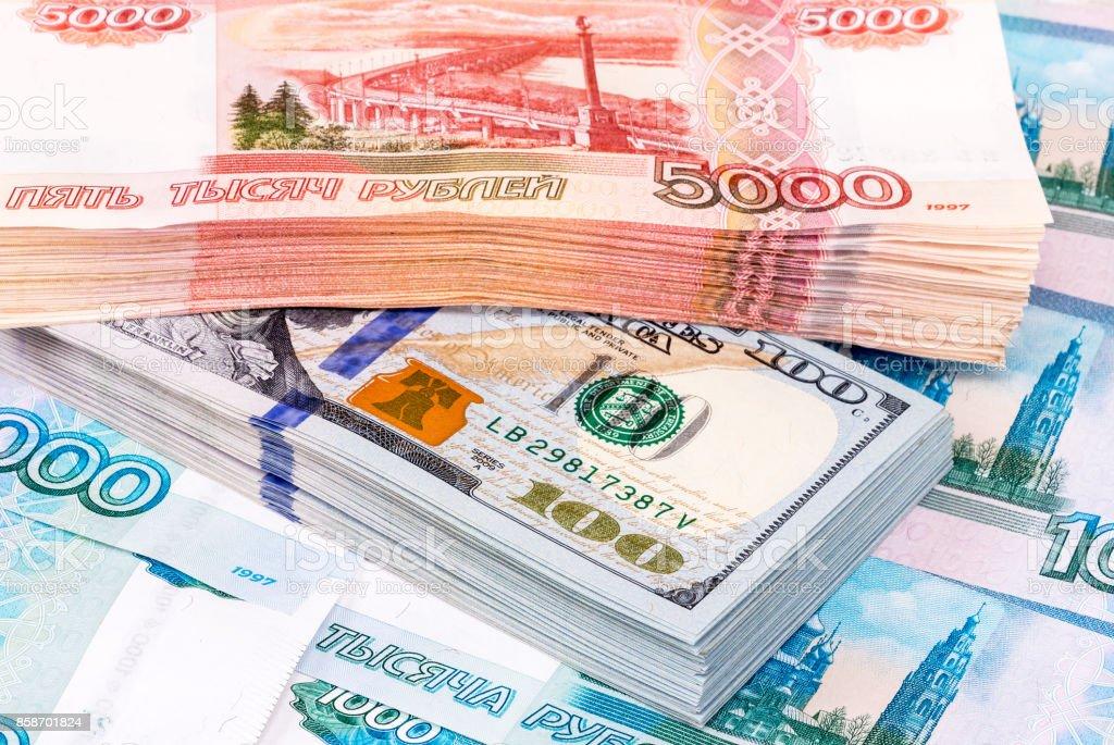 Pila de billetes de dólar y cinco milésimas billetes de rublos rusos - foto de stock