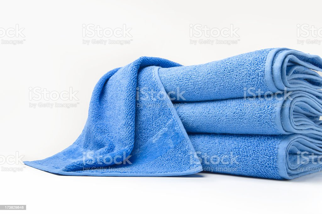 Stack of folded blue cotton towels with one draped on top stock photo