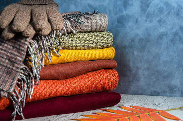 Stack of folded knitted women's sweaters in warm colors, scarf, gloves and autumn leaves on gray background. Copy space Stack of folded warm knitted women's sweaters in warm colors, plaid scarf, knitted gloves and autumn leaves on gray background. Copy space. Closeup warm clothing stock pictures, royalty-free photos & images