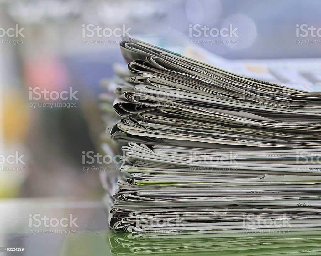Stack of folded news papers on blurry background stock photo