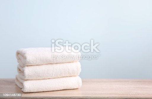 Stack of white terry towels on wooden table empty space background.