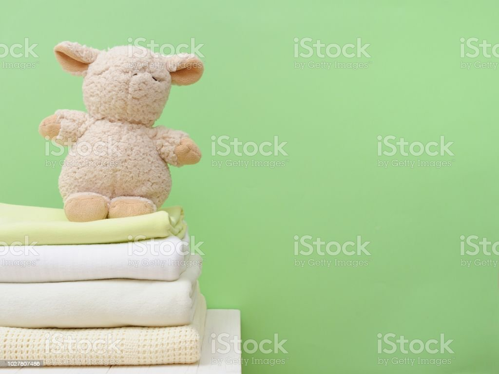 Cozy plush stuffed toy lamb resting on soft warm blankets concept for...