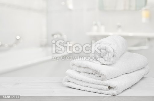 istock Stack of folded white spa towels over blurred bathroom background 515812174