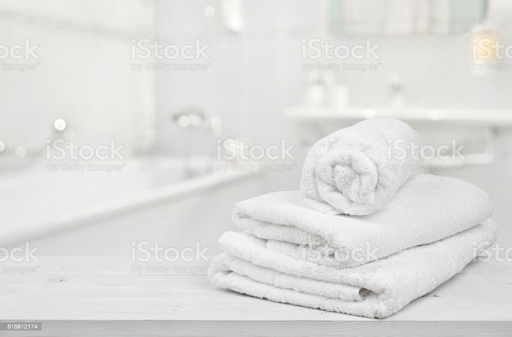 Stack of folded white spa towels over blurred bathroom background stock photo