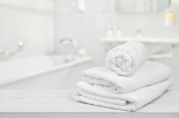 stapel gefaltet weiß spa-handtücher auf hintergrund verschwommen badezimmer - hausmittel gegen falten stock-fotos und bilder