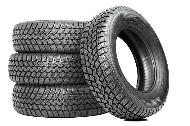 stack of four black car tires isolated on white - autoband stockfoto's en -beelden