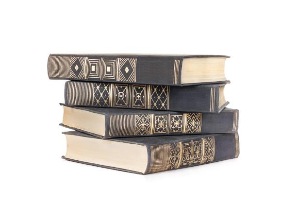 pilha de quatro livros em uma capa de tecido preto isolado em um fundo branco - foto de acervo