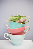 a pile of breakable and fragile pastel teacups balancing one on top of each other on top on a white table in front of a light blue background