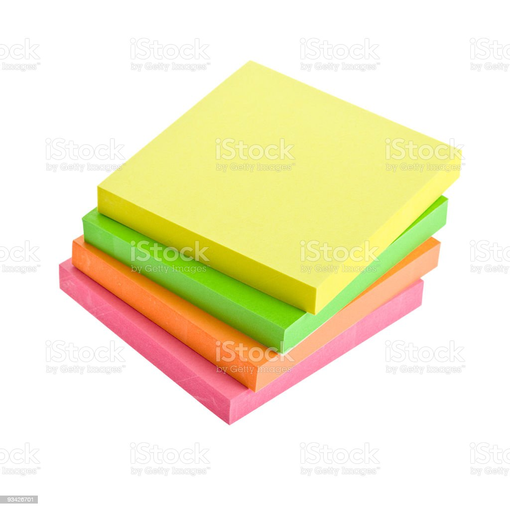 A stack of four sticky note pads in different colors stock photo