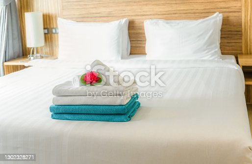 Stack of fresh white and blue towels with red lotus flower on white bed in bedroom.