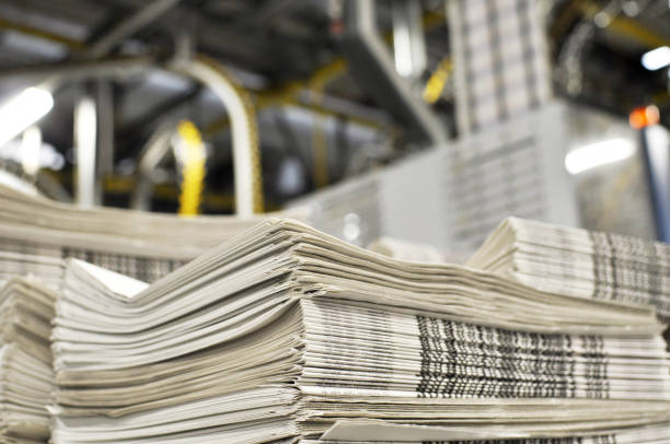 stack of freshly printed daily newspapers transported to a printing plant, in the background machines and technical equipment of a large printing plant stack of freshly printed daily newspapers transported to a printing plant, in the background machines and technical equipment of a large printing plant printing plant stock pictures, royalty-free photos & images