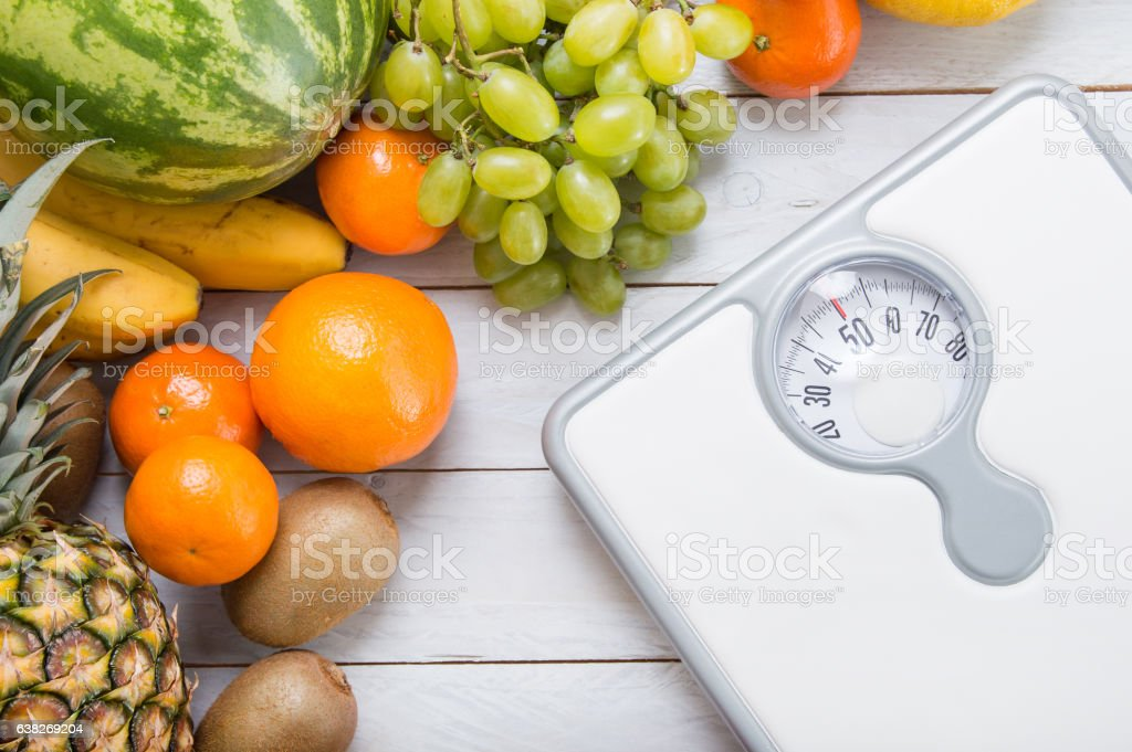 Stack of fruits and white weight scale on wooden board. stock photo