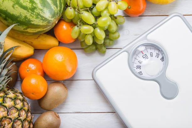 stack of fruits and white weight scale on wooden board. - weights stock photos and pictures