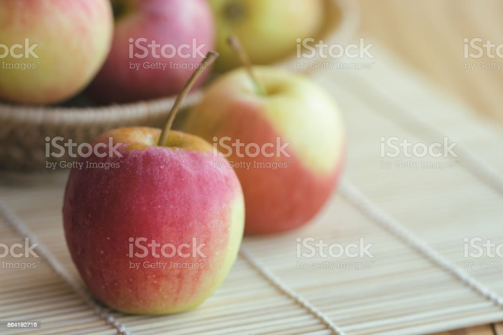Stack of fuji apple in basket and on wood table for background or wallpaper. Delicious sweet and juicy fuji apple suitable for salad cooking or bakery. Fuji apple has origins in Japan. royalty-free stock photo