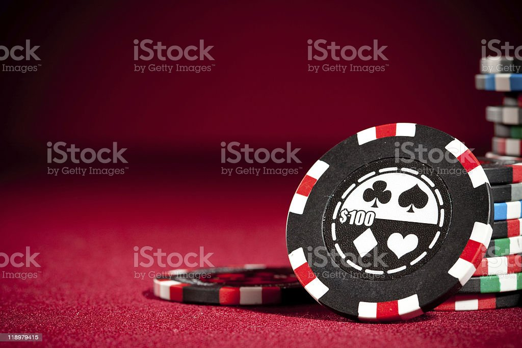A stack of gambling chips on a red carpet surface stock photo