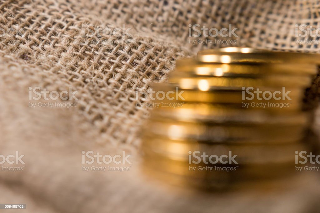 Stack of gold coins on jute background blurred stock photo