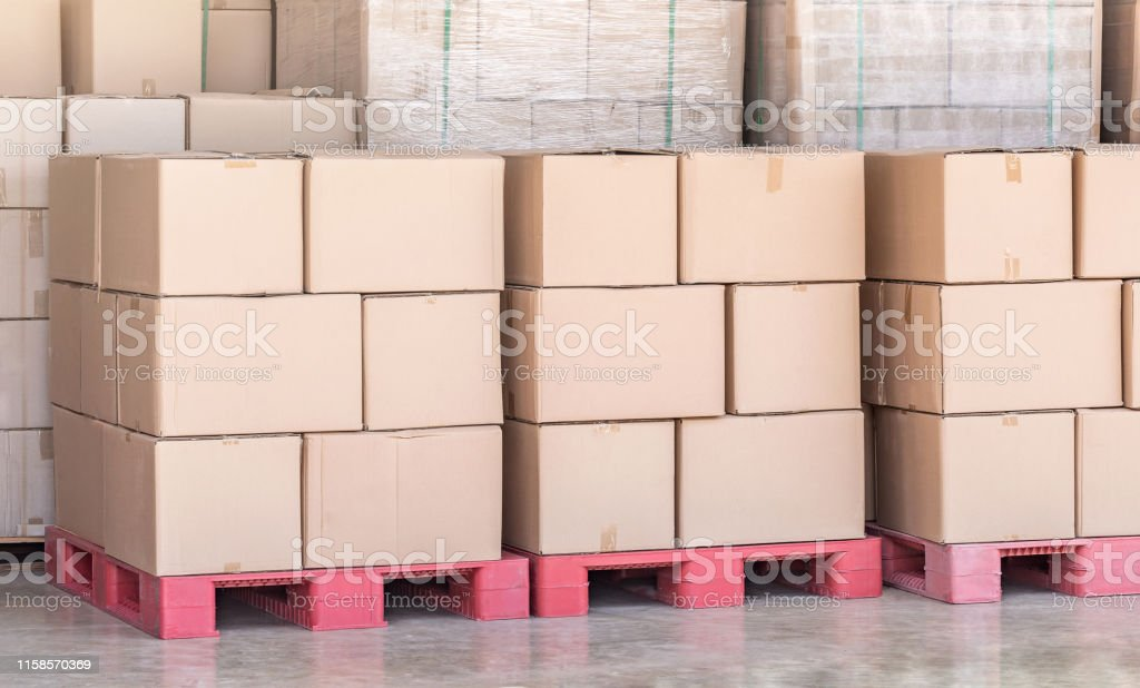 Stack of goods carton boxes on red pallet at logistics warehouse...