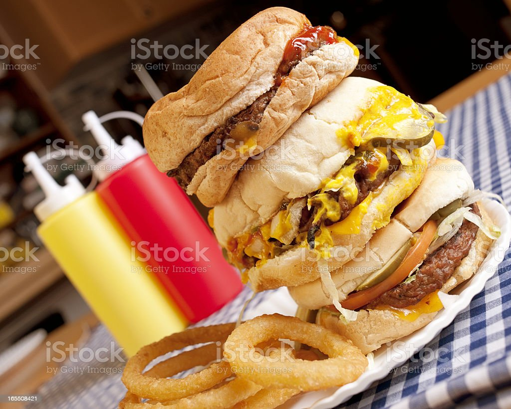 Stack of hamburgers with onion rings and mustard bottle stock photo