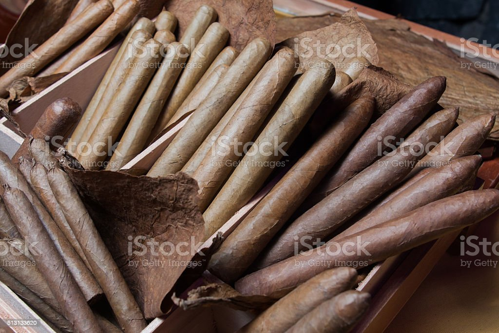 stack of hand made cigars parejos on wooden table stock photo