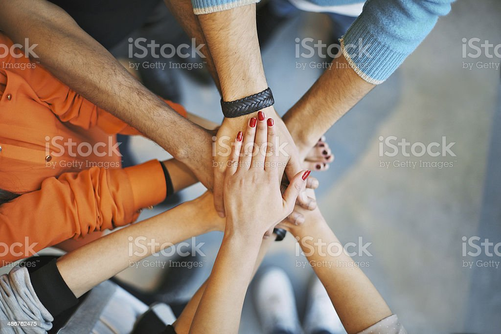 Stack of hands a teamwork symbol stock photo