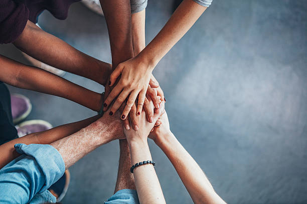 Stack of hands showing unity Close up top view of young people putting their hands together. Friends with stack of hands showing unity. hand stock pictures, royalty-free photos & images