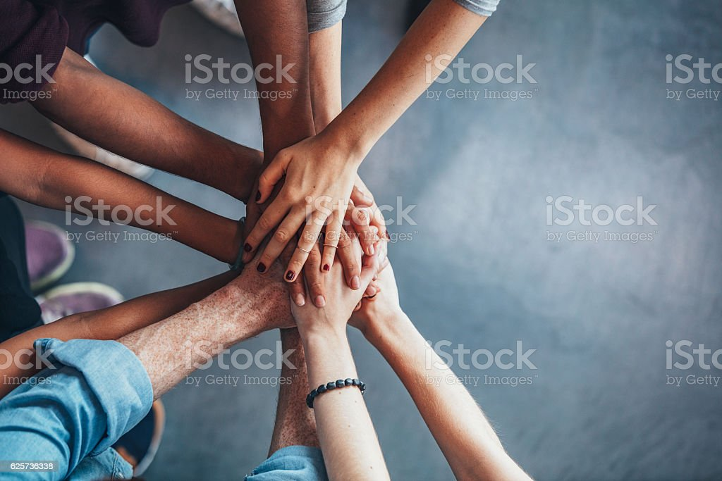 Stack of hands showing unity bildbanksfoto