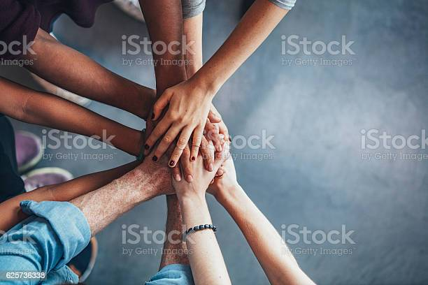 Close up top view of young people putting their hands together. Friends with stack of hands showing unity.