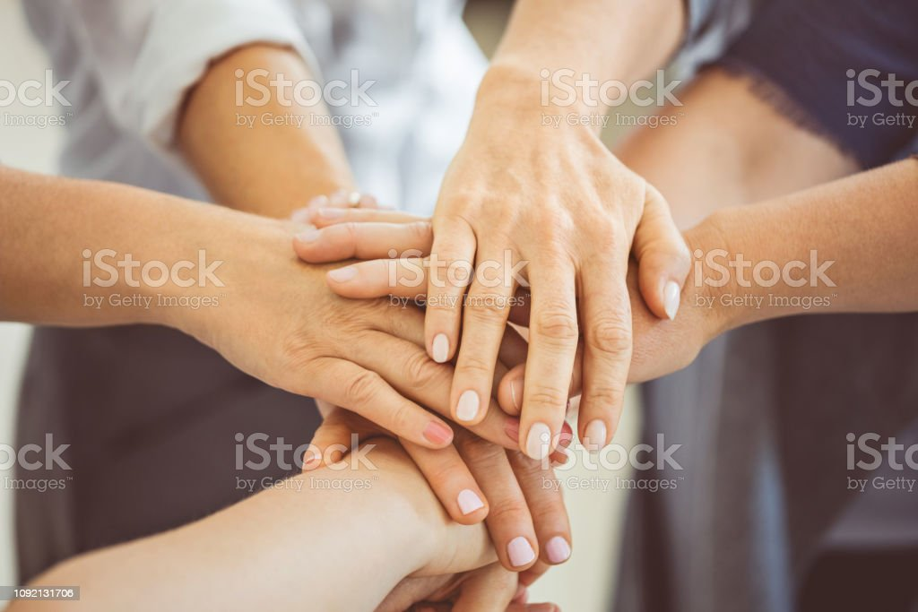 Stack of hands symbolizing teamwork and cooperation Group of females putting their hands together. Close up of female hands stack symbolizing teamwork and cooperation A Helping Hand Stock Photo