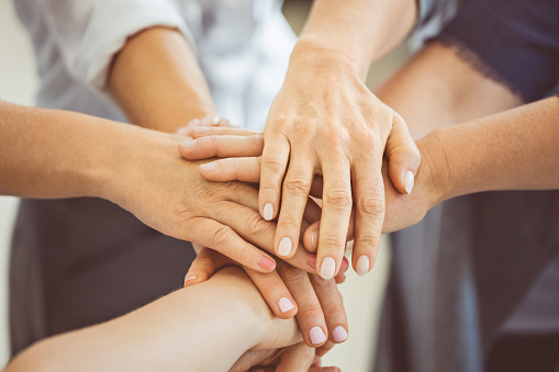 Stack Of Hands Symbolizing Teamwork And Cooperation Stock Photo - Download Image Now