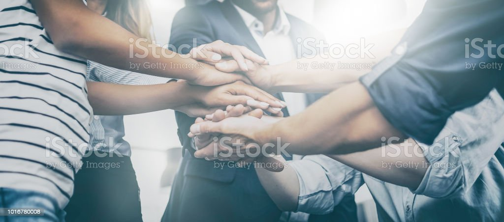 Stack of hands. Unity and teamwork concept. Close up view of young business people putting their hands together. Stack of hands. Unity and teamwork concept. A Helping Hand Stock Photo