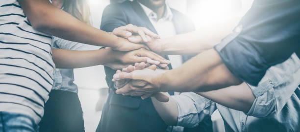 Stack of hands. Unity and teamwork concept. Close up view of young business people putting their hands together. Stack of hands. Unity and teamwork concept. collaboration stock pictures, royalty-free photos & images