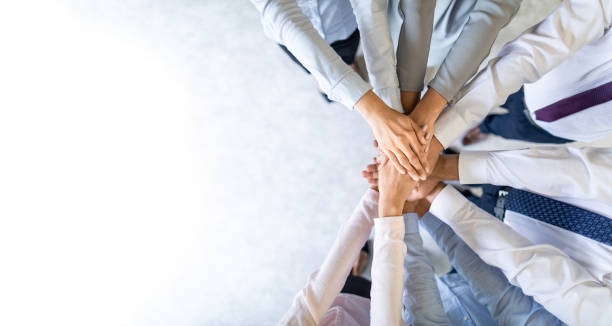 Stack of hands. Unity and teamwork concept. Close up top view of young business people putting their hands together. Stack of hands. Unity and teamwork concept. group corporate stock pictures, royalty-free photos & images