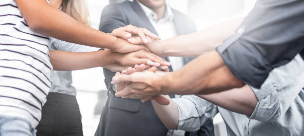Stack of hands. Unity and teamwork concept. Close up view of young business people putting their hands together. Stack of hands. Unity and teamwork concept. business stock pictures, royalty-free photos & images