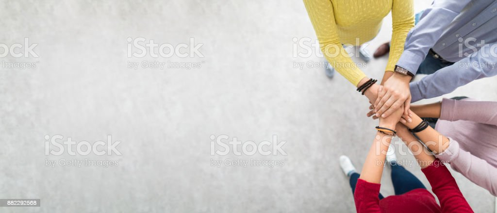 Stack of hands. Unity and teamwork concept. Close up top view of young business people putting their hands together. Stack of hands. Unity and teamwork concept. A Helping Hand Stock Photo
