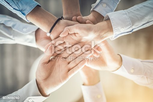 istock Stack of hands. Unity and teamwork concept. 922659740