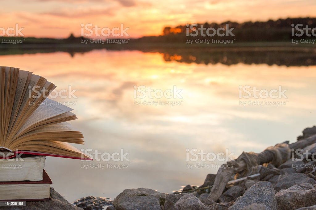 Stack of hardback book, Open  book on blurred nature landscape stock photo