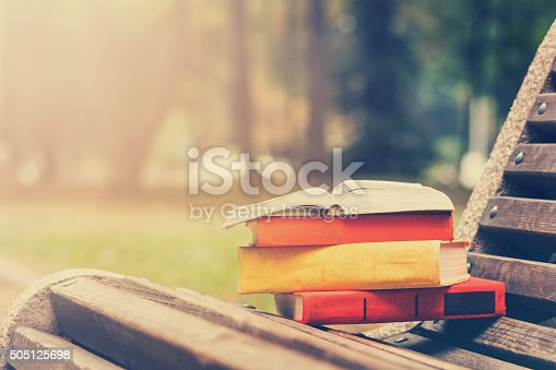 istock Stack of hardback books and Open book lying on bench 505125698