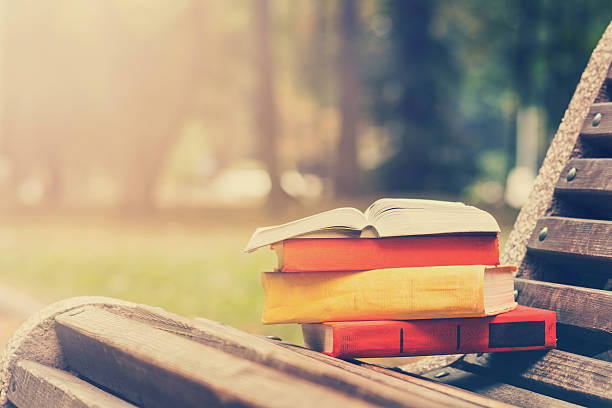 Stack of hardback books and Open book lying on bench stock photo