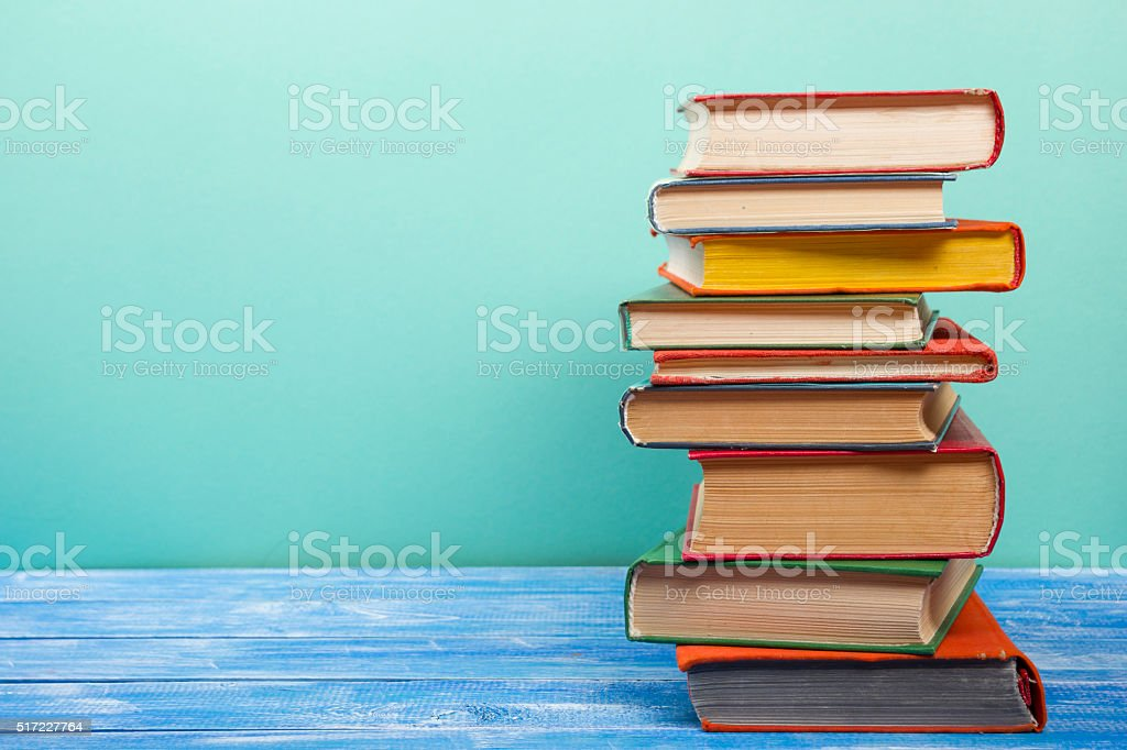 Stack of hardback books on wooden table. Back to school stock photo