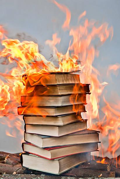 stack of hardcover burning books stock photo