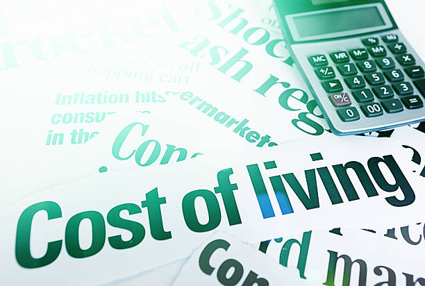 Stack of headlines on Cost of Living plus calculator stock photo