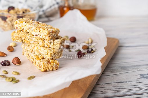 Stack of healthy homemade granola bars with nuts, honey and dried fruit on wooden table in the kitchen