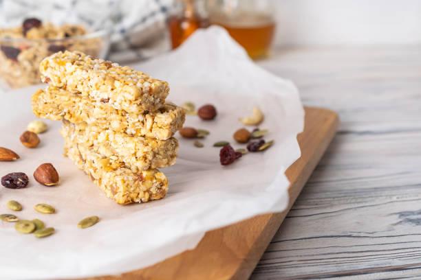 stapel gezonde zelfgemaakte granola repen met noten, honing en gedroogd fruit op houten tafel - kauwgomachtig stockfoto's en -beelden