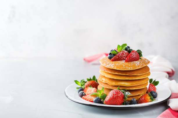 stack of homemade pancakes for breakfast with berries - miele dolci foto e immagini stock