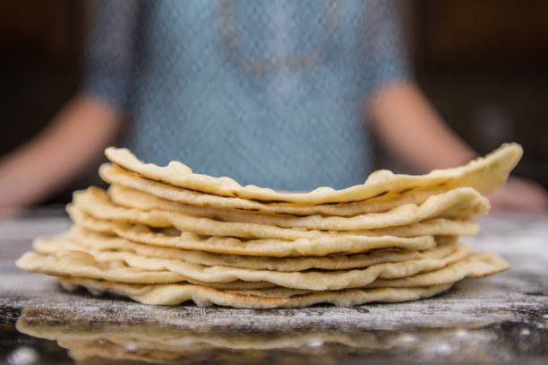 stack of homemade tortillas on floured surface - tortilla stock photos and pictures